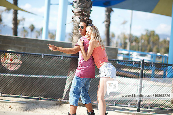 Couple rollerblading outdoors  woman holding man's shoulders  rear view