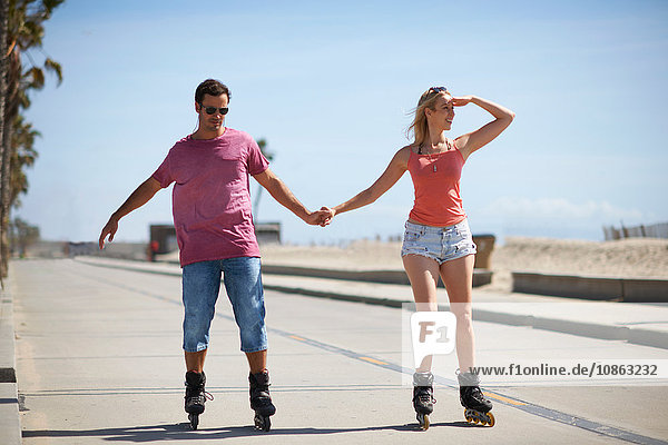 Couple rollerblading outdoors  holding hands