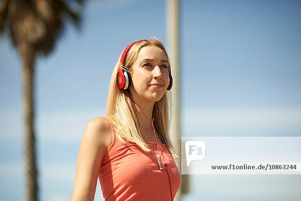 Porträt einer jungen Frau im Freien  die Kopfhörer trägt