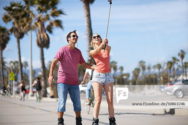 Couple rollerblading outdoors  taking self portrait  using selfie stick
