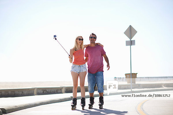 Couple rollerblading outdoors  woman holding selfie stick