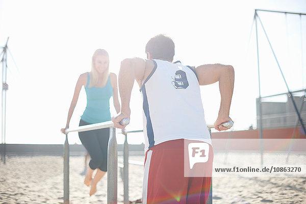 Paarübungen am Strand  mit Gymnastikbalken