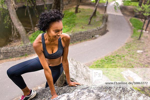 Frau in Sportkleidung beim Klettern am Fels