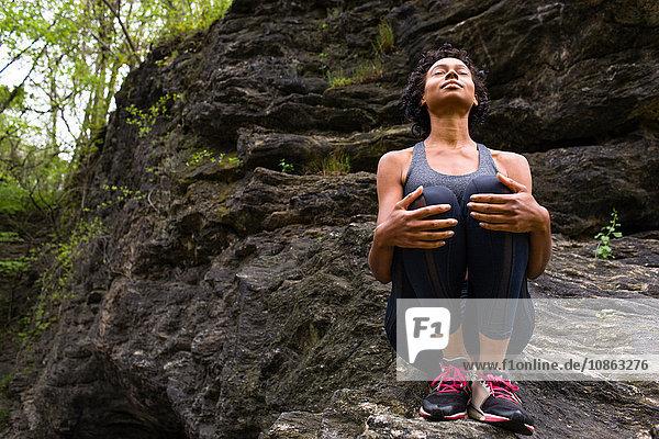 Frau sitzt kniend auf Felsen und meditiert