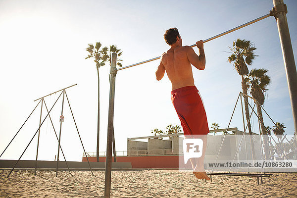 Mid adult man exercising on beach  using gymnastics training bar  rear view