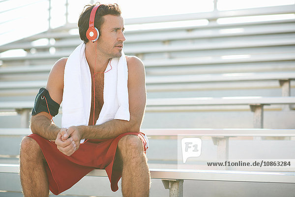 Mid adult man sitting on bench  taking a break from exercise  wearing headphones  towel around neck