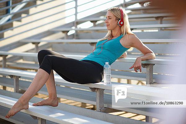 Junge Frau macht eine Pause vom Sport  sitzt auf einer Bank und trägt Kopfhörer