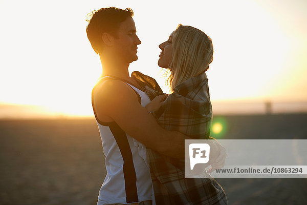 Couple hugging outdoors  at sunset  face to face  young woman wrapped in blanket