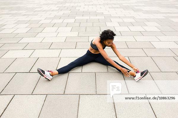 Frau sitzt auf dem Bürgersteig mit gespreizten Beinen und macht Dehnungsübungen