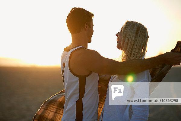 Ehepaar am Strand  bei Sonnenuntergang  Mann legt Decke um junge Frau