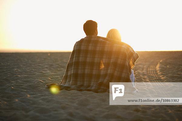 Paar am Strand  in eine Decke gewickelt  Sonnenuntergang beobachtend  Rückansicht