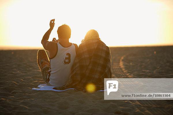 Paar am Strand  bei Sonnenuntergang  junge Frau in eine Decke gewickelt  Rückansicht