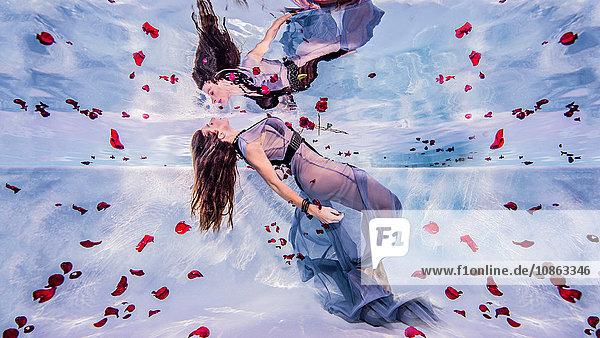 Frau unter Wasser mit Rosenblättern
