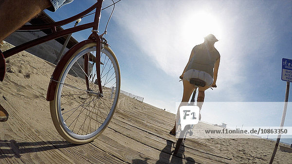 Low angle view of couple cycling on boardwalk at Venice Beach  California  USA