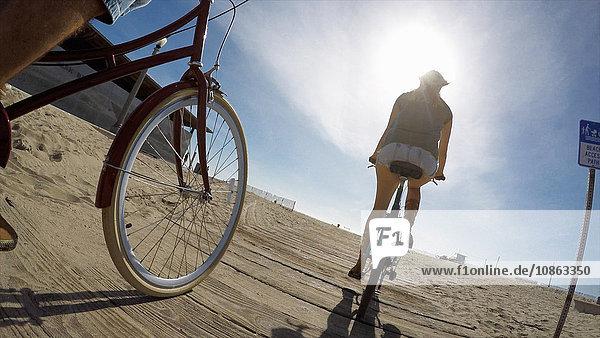 Niedrigwinkelaufnahme eines Paares beim Radfahren an der Strandpromenade von Venice Beach  Kalifornien  USA