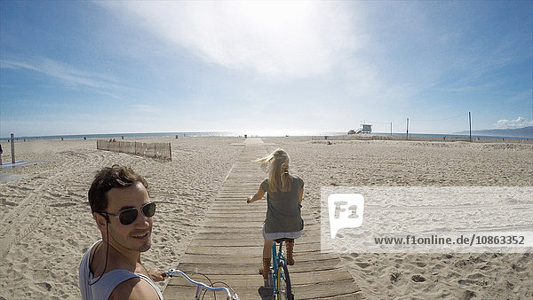 Man taking selfie cycling on Venice Beach boardwalk  California  USA