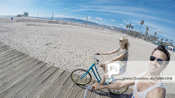 Couple taking selfie cycling on Venice Beach boardwalk  California  USA