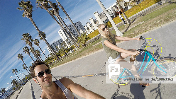 Man taking selfie cycling with girlfriend at Venice Beach  California  USA