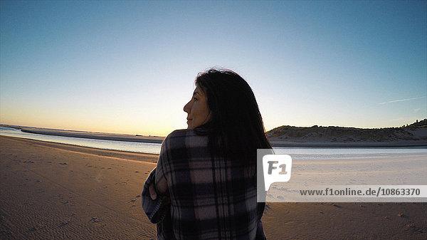 Rückansicht einer in ein Tuch gehüllten Frau  die am Cannon Beach  Oregon  USA  wegschaut