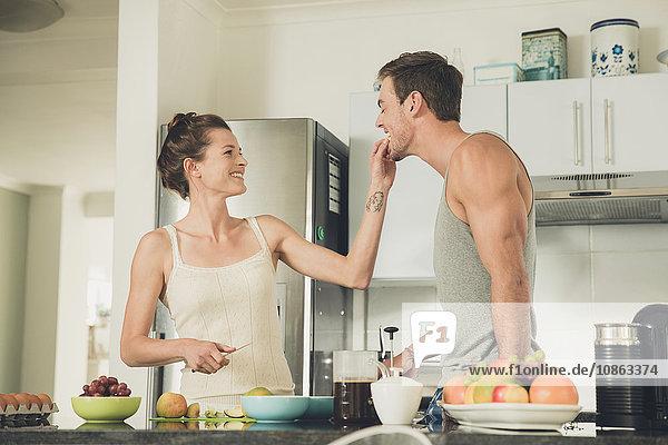 Junge Frau füttert ihren Freund an der Küchentheke mit Obst