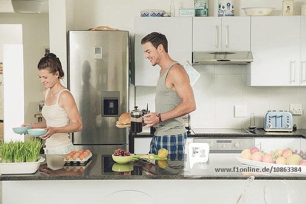 Junges Paar trägt Frühstück von der Küchentheke