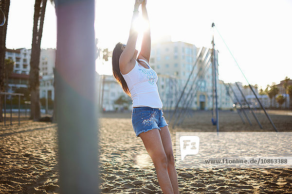 Frau am Strand in Jeans-Shorts und angehobenen Westenarmen  zurückgelehnt