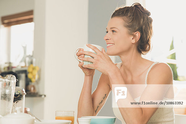 Young woman drinking coffee at breakfast table