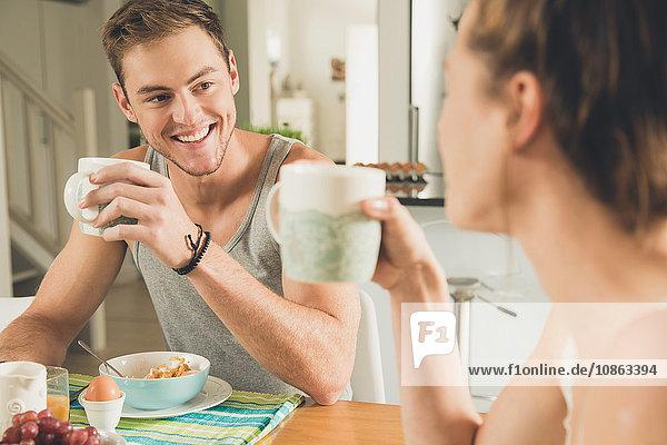 Junges Paar trinkt Frühstückskaffee am Küchentisch