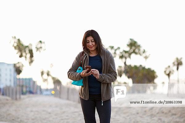 Frau mit Handtasche trägt Handtasche und schaut lächelnd auf Smartphone