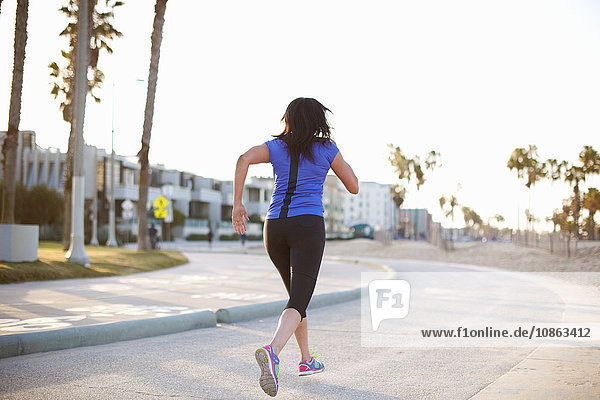 Full length rear view of woman wearing sports clothes jogging in road
