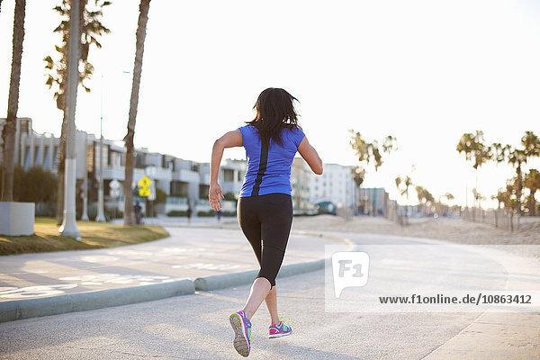 Rückansicht einer Frau in Sportkleidung in voller Länge  die auf der Straße joggt