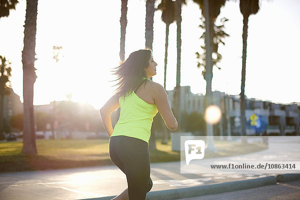 Side view of woman wearing neon vest jogging