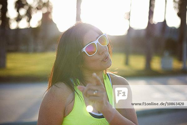 Frau mit Neonweste und Sonnenbrille schaut in die Kamera und wedelt mit dem Finger