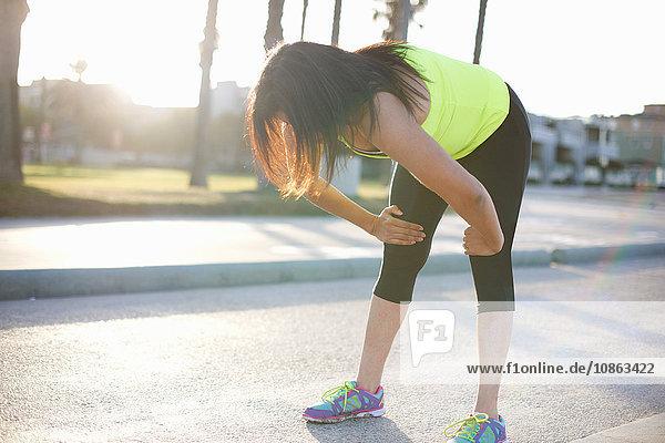Frau in Sportkleidung Hände auf Knien nach vorne gebeugt