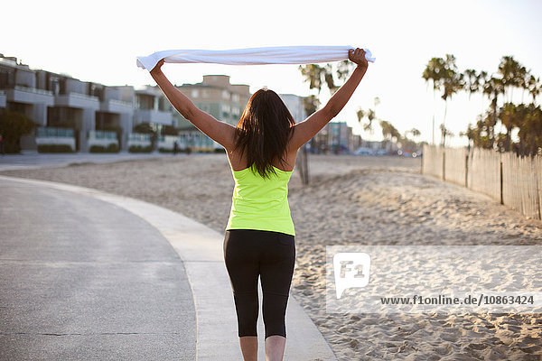 Rückansicht einer Frau in Sportkleidung mit erhobenen Armen  die ein Handtuch hält