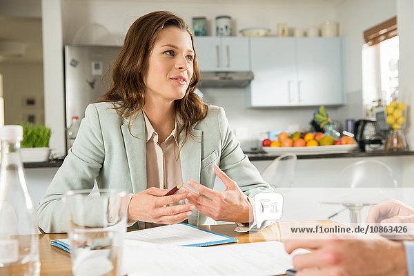 Junge Frau am Küchentisch  die ihrem Freund Rechnungen erklärt