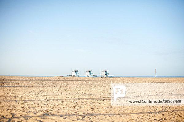 Drei Rettungsschwimmertürme am leeren Strand