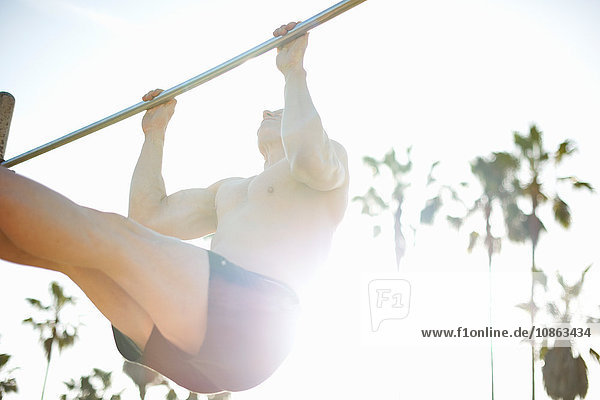 Low angle view of man  legs raised doing pull up on gymnastic bar