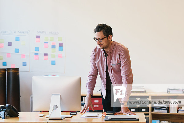 Man in office leaning against desk looking at computer monitor