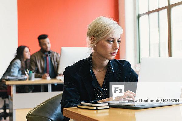 Woman in office using laptop