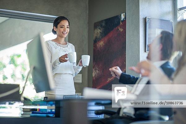 Büroangestellter  der dem Geschäftsteam am Büroschreibtisch Kaffee reicht