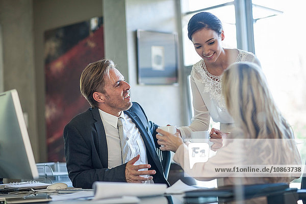 Office worker handing coffee to businessman and woman at office desk