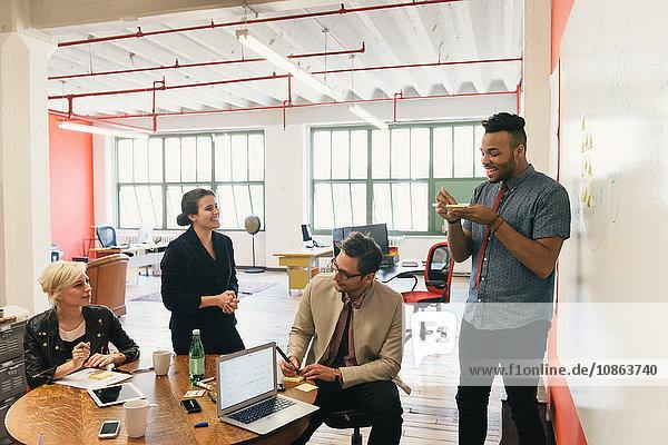 Kollegen im Büro am Tisch plaudern
