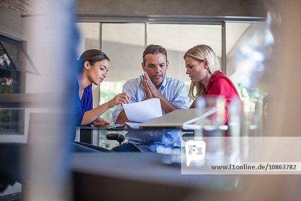 Drei Designer treffen sich am Konferenztisch im Designbüro