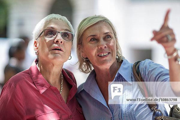 Zwei reife Frauen  die auf die Stadt zeigen und aufschauen