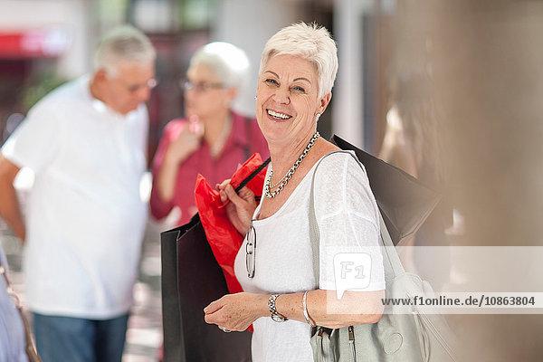 Porträt einer älteren Frau mit Einkaufstaschen in der Stadt