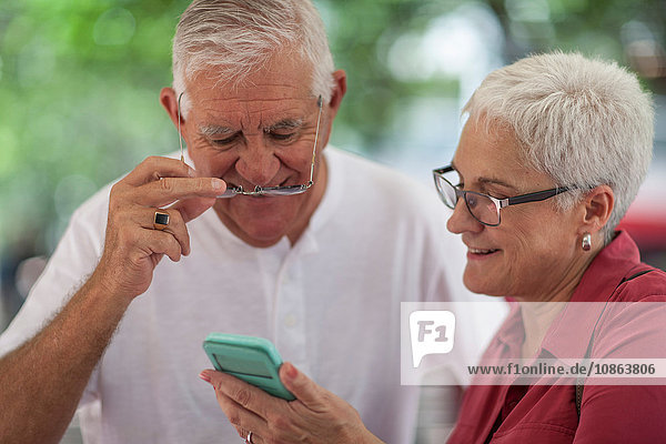 Senior man and woman wearing spectacles reading smartphone in city