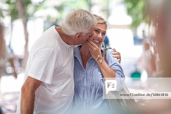 Älterer Mann küsst Frau in der Stadt auf die Wange