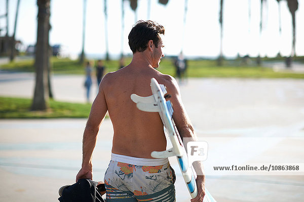 Rear view of man carrying surfboard at Venice Beach  California  USA