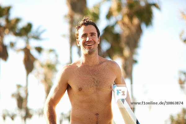 Male surfer carrying surfboard at Venice Beach  California  USA
